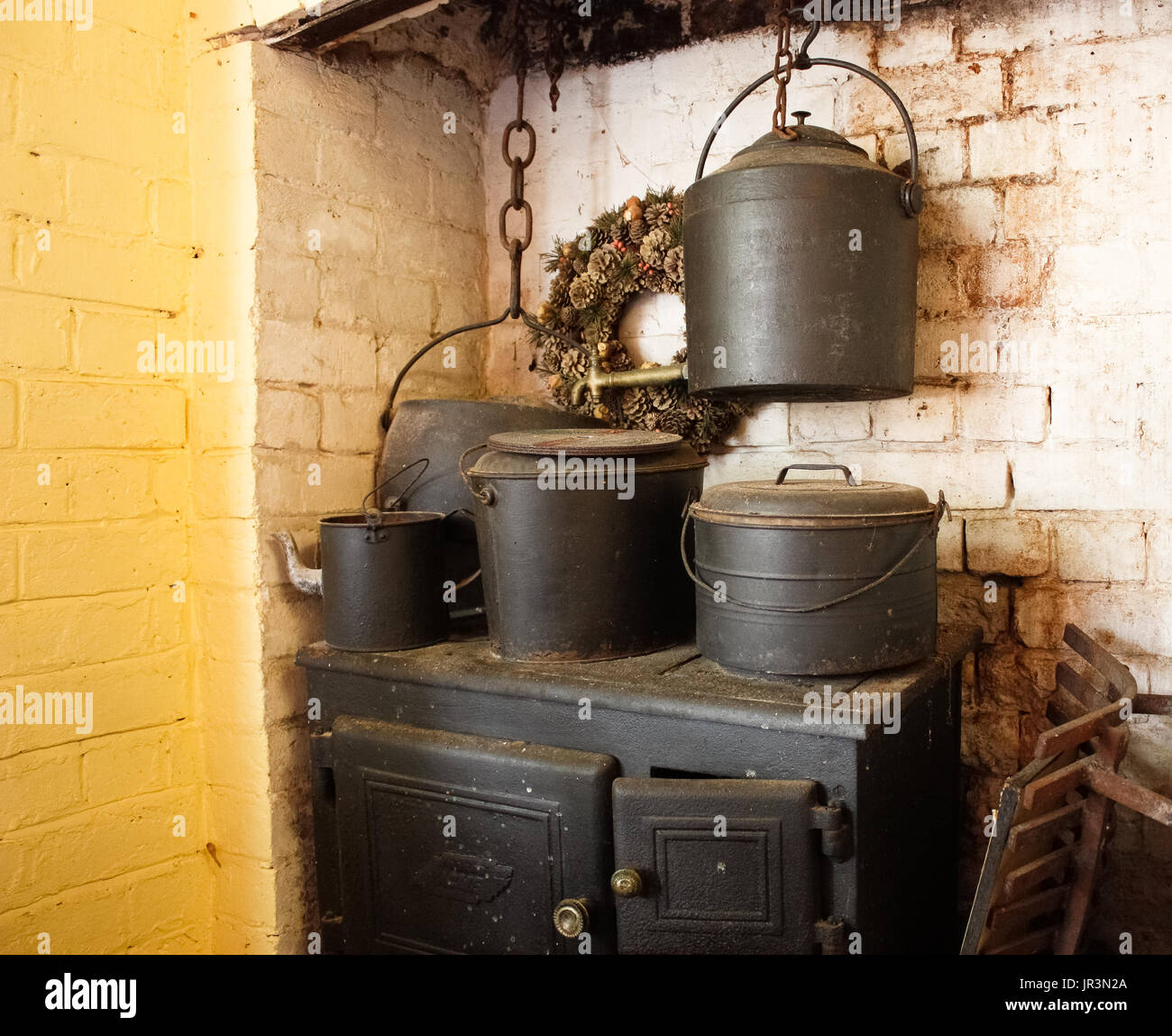 Old fashioned wood cooking stove with cast iron pots against brick wall - Stock Image