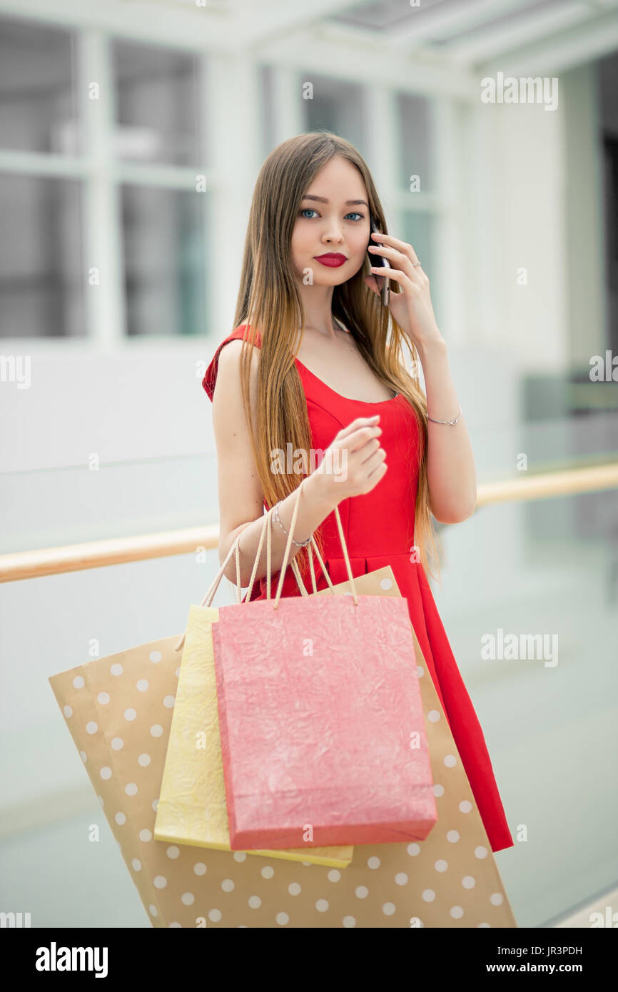 874ab594fe Technologies make shopping easier. Beautiful young woman with shopping bags  using her smart phone with smile while standing at the clothing store