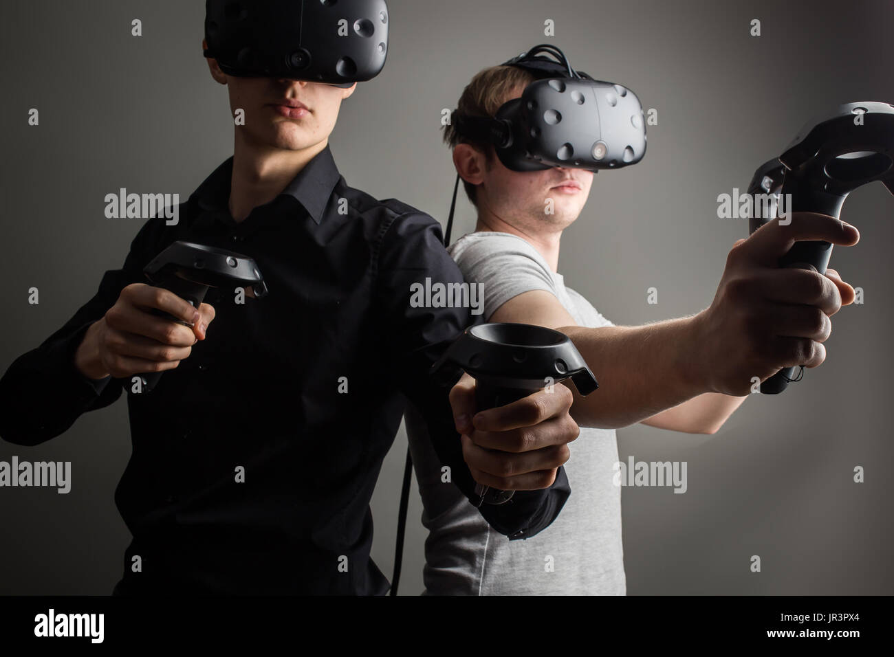 Shot of two young man standing with VR goggles and keep