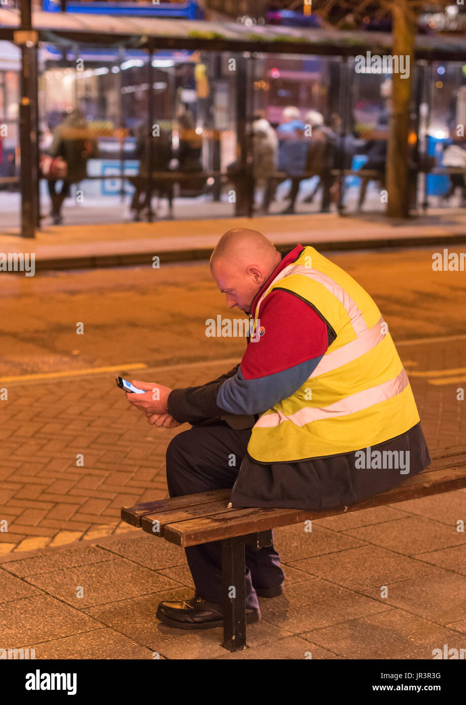 Bus driver  wearing a uniform sitting on a bench reading his mobile phone on the street at night in Canterbury, Kent. - Stock Image