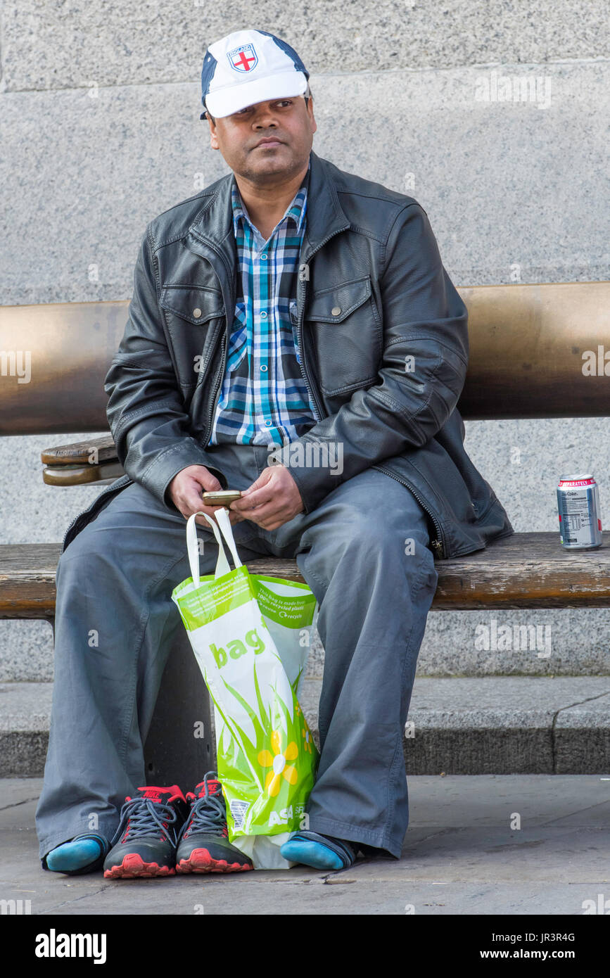An asian male wearing an England baseball cap sitting by himself holding his mobile phone in London, UK. - Stock Image