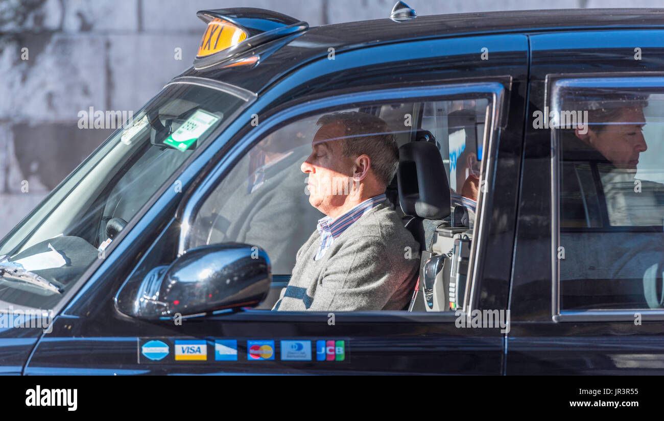 A black cab driver resting at the wheel in busy traffic in London with a male passenger behind him. The taxi has pictures of credit cards on the door. - Stock Image