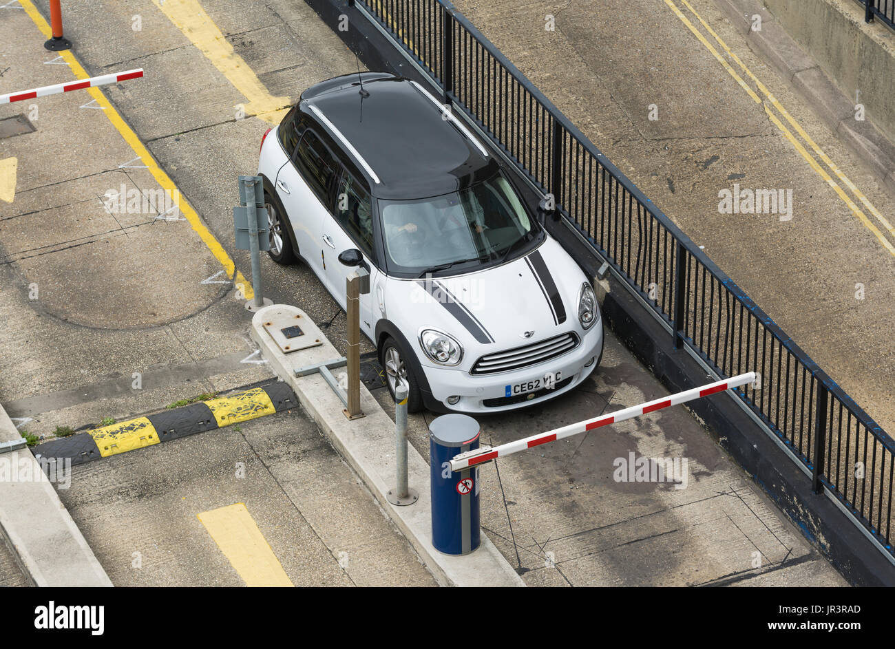 Car waiting at a lowered barrier at the entrance of a multi storey car park in the UK. - Stock Image