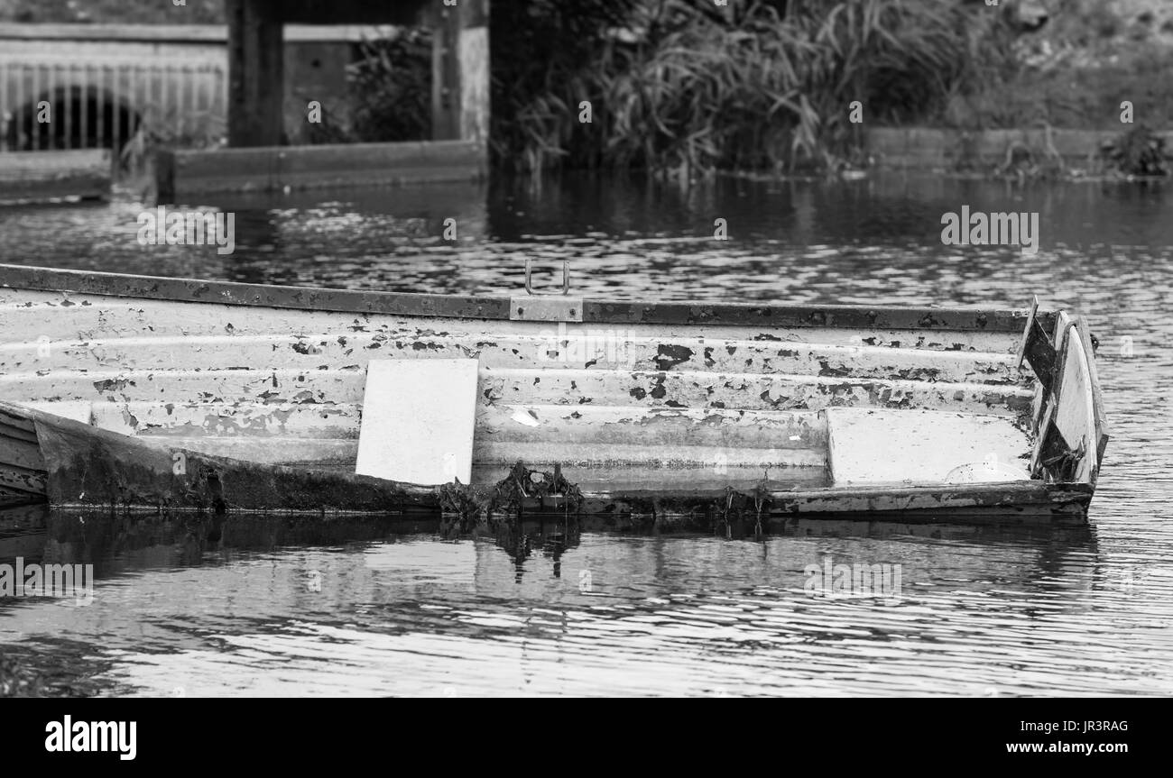 Small wooden boat abandoned in a lake and half under water. Black and white. Stock Photo