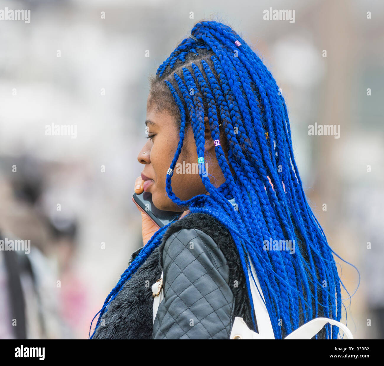 Young black woman with braided blue hair. - Stock Image