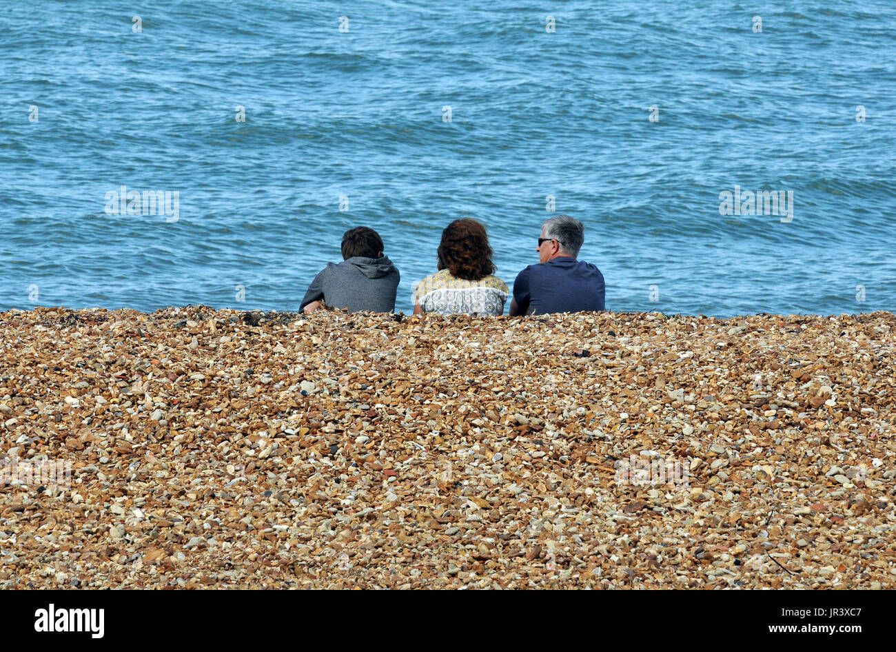 a family sitting on a stony beach at the seaside looking out to sea and in conversation with each other sea front pebbles and summer holidays families - Stock Image