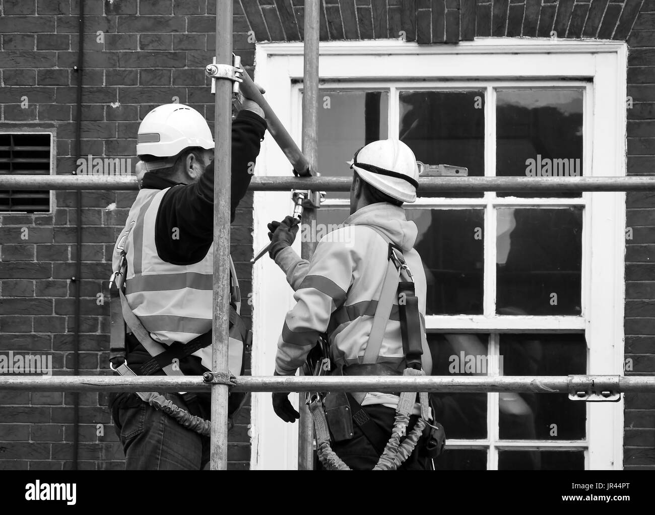 Two workers assembling scaffolding on city building - Stock Image
