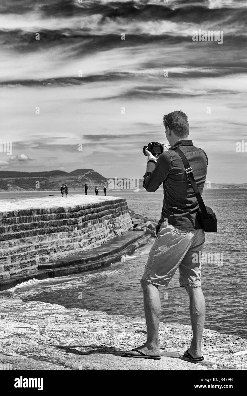 Man photographer taking photos photographs of visitors on The Cobb at Lyme Regis, Dorset in July - Stock Image