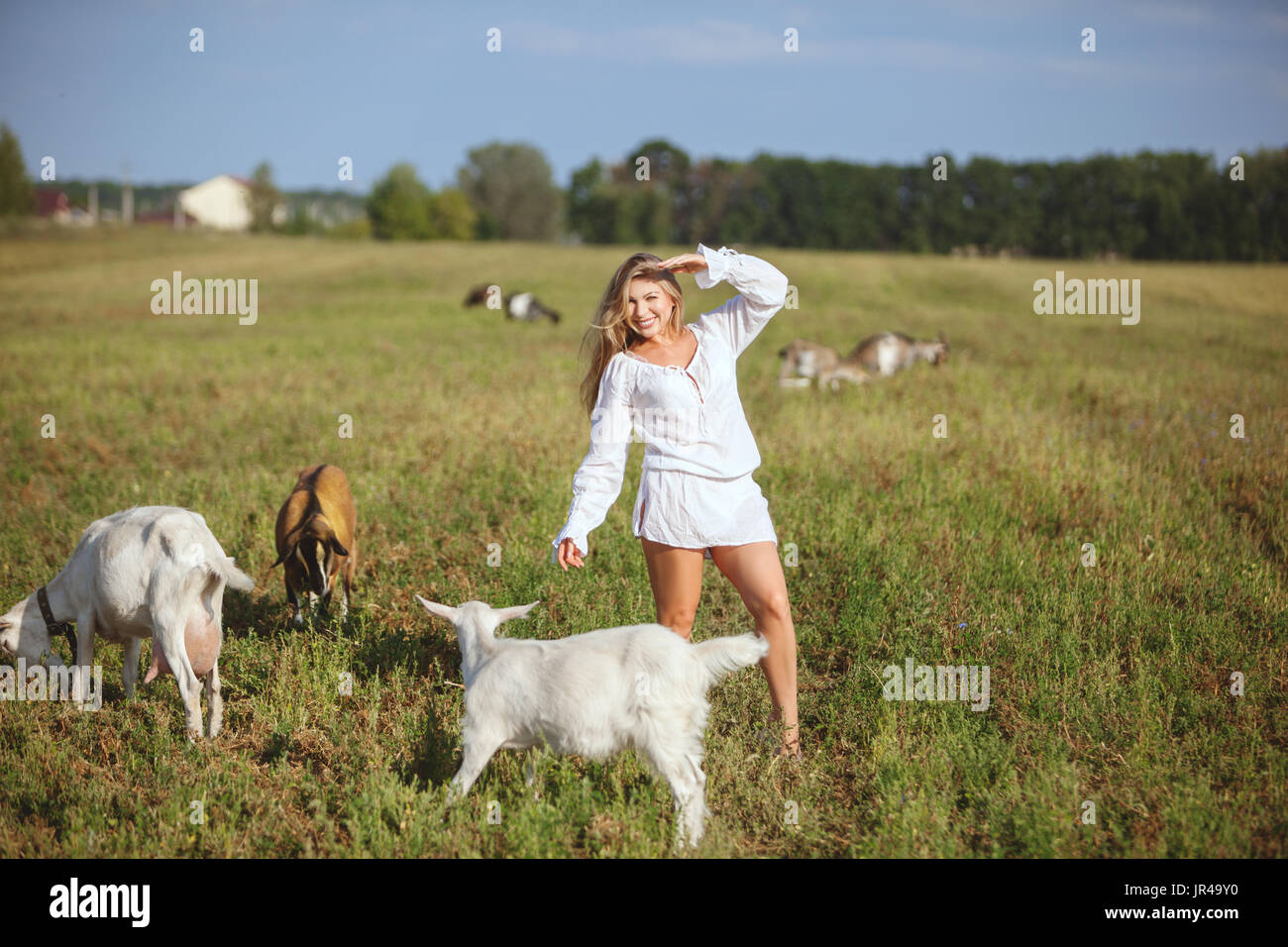In the field to graze domestic goats, next to a happy woman and smiling. - Stock Image