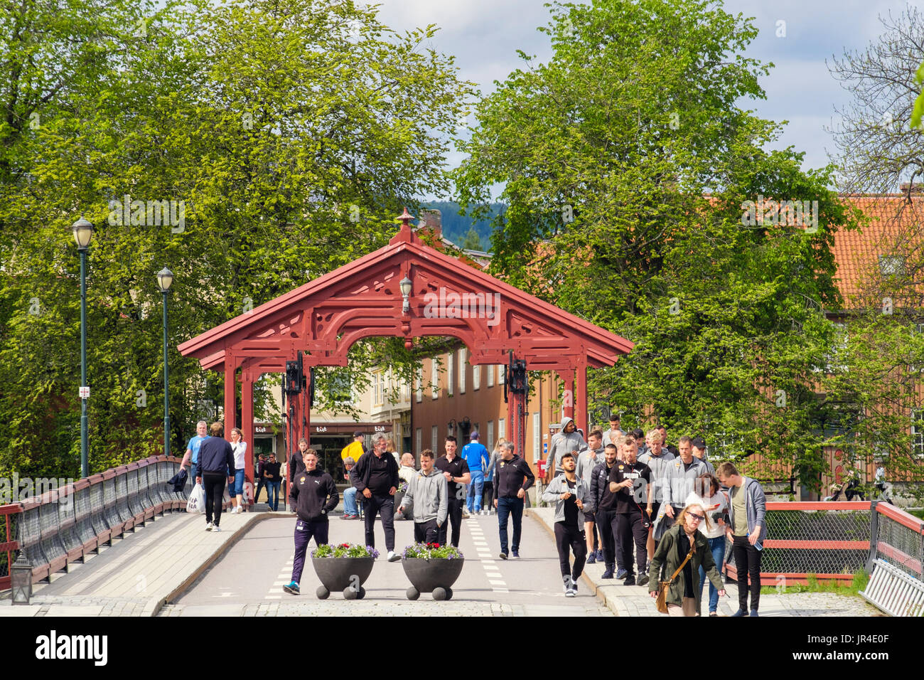 People crossing the Old Town Bridge (Gamle Bybro) with a Lykkens portal (1861). Trondheim, Sør-Trøndelag, Norway, Stock Photo