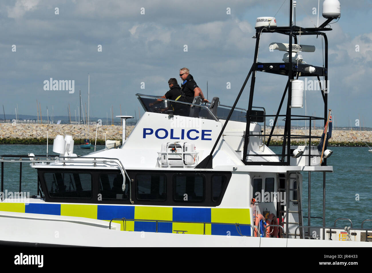 police officers at cowes week on the isle of wight policing on the beat and policing on the water in a police boat or launch stab vests body protector - Stock Image