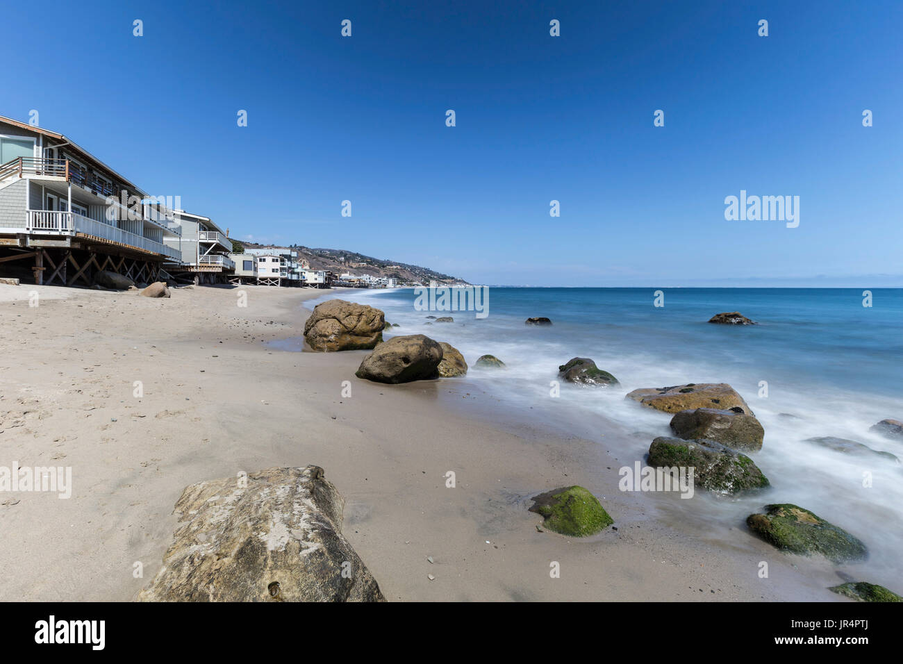 Oceanfront homes with motion blur water movement at Carbon Beach in Malibu, California. - Stock Image