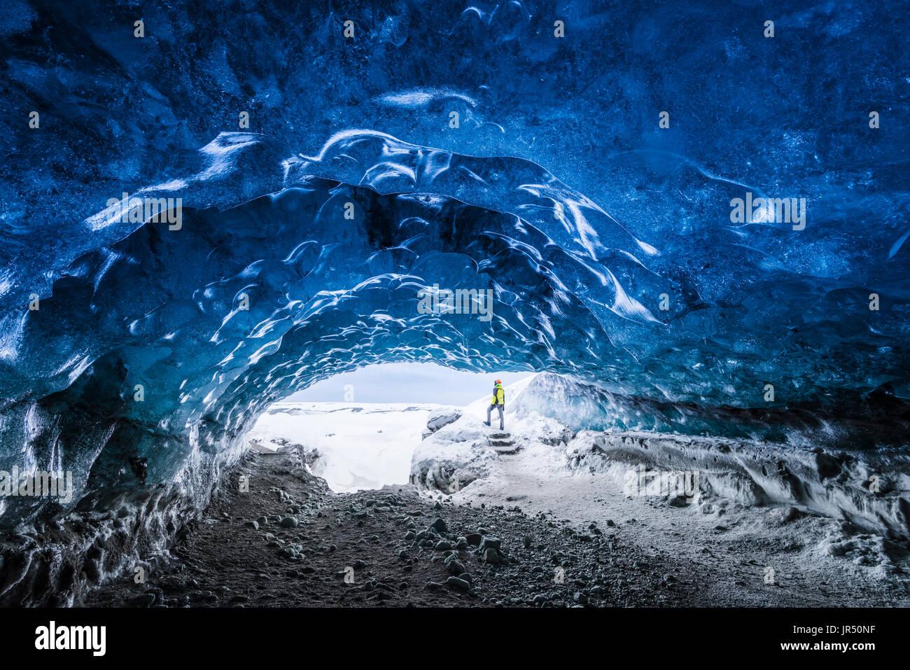 Man inside an ice caver under the Vatnajokull glacier, Vatnajokull national park, East Iceland, Iceland. - Stock Image