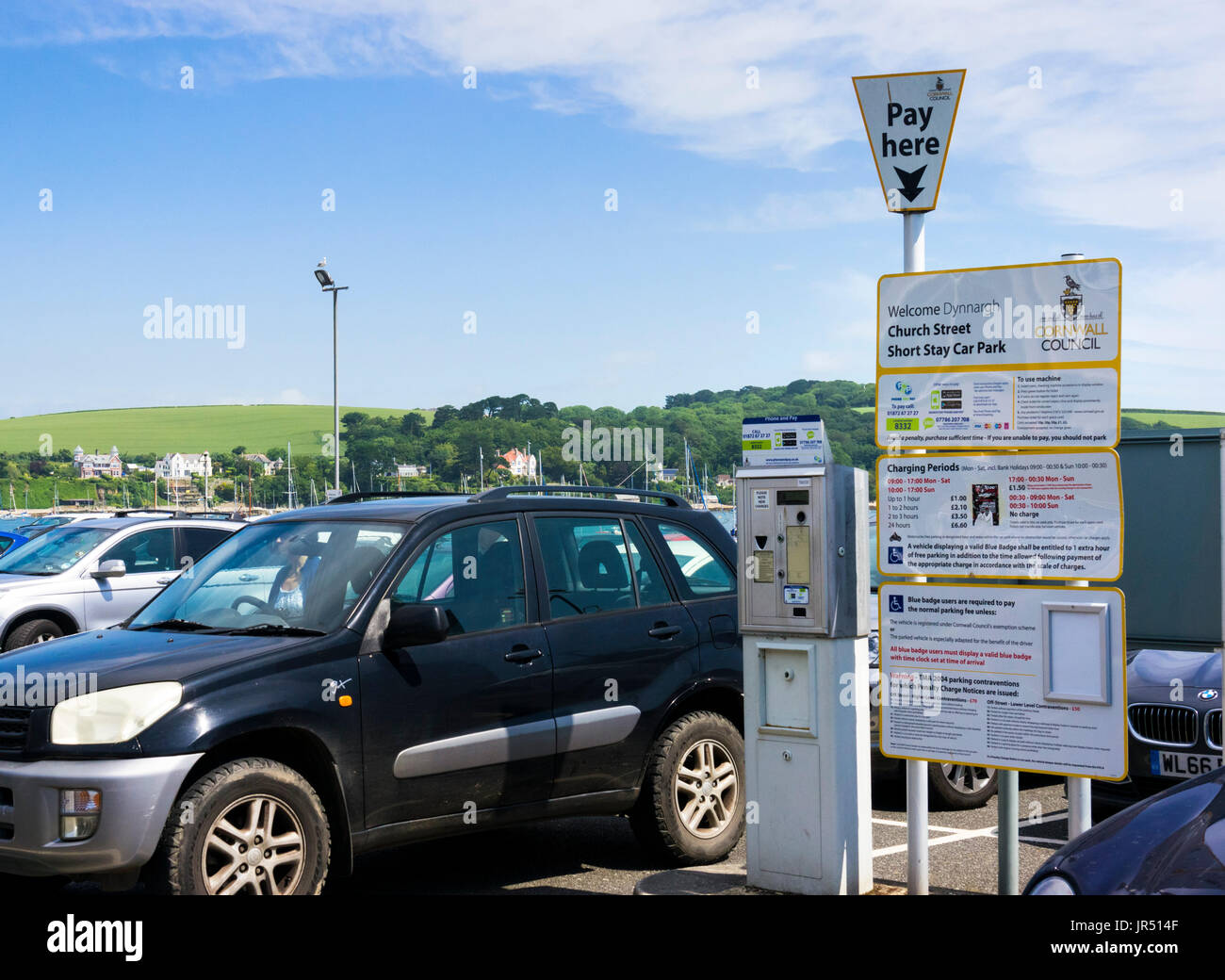 Short stay car park full of cars in summer, with pay here machine and charges, England, UK - Stock Image