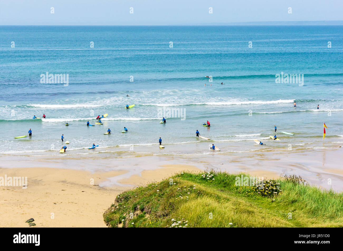 Surfing school with people learning to surf at Poldhu Cove UK beach, Cornwall, UK - Stock Image