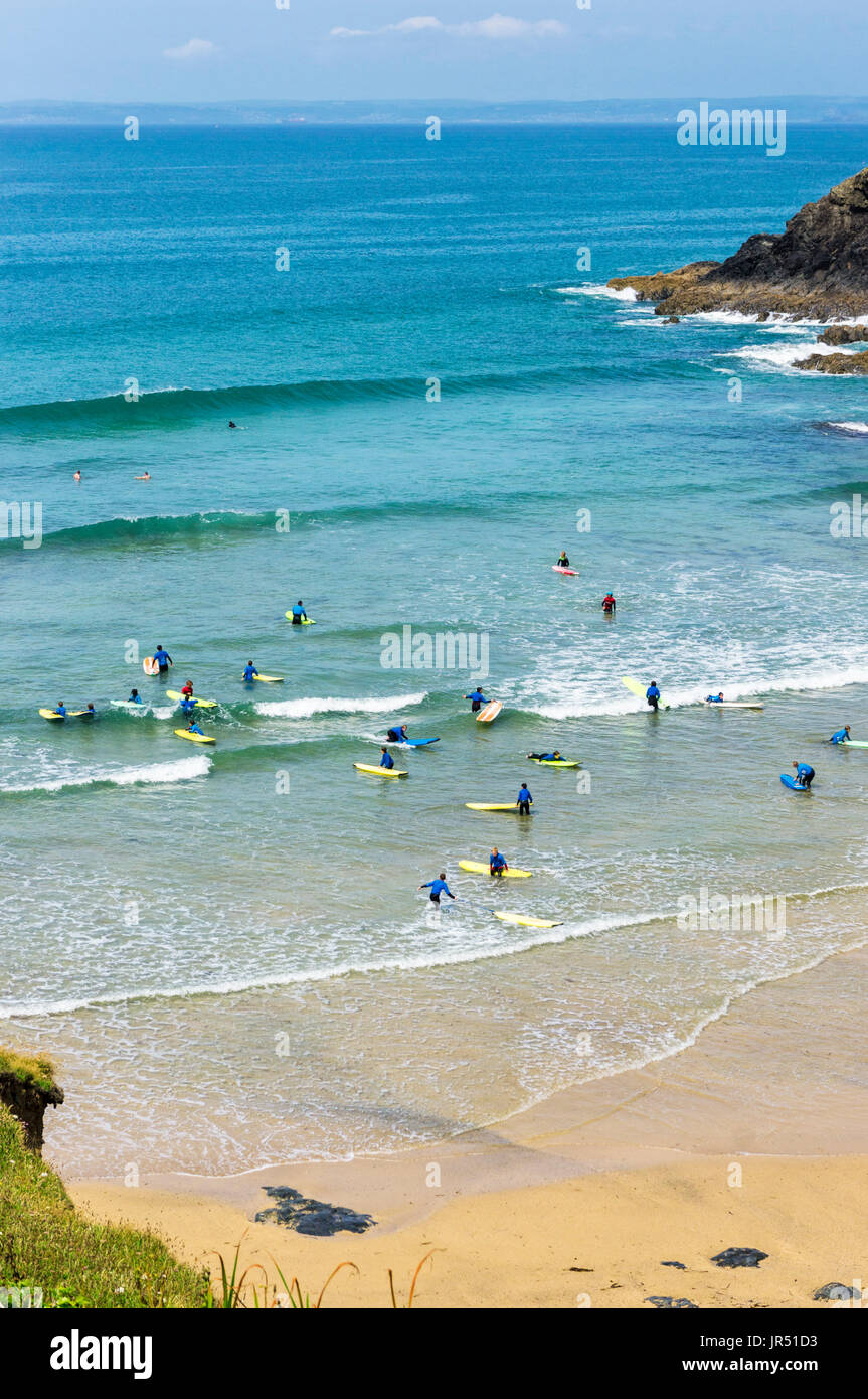 Surfing school with people learning to surf at Poldhu Cove beach, Cornwall, UK - Stock Image