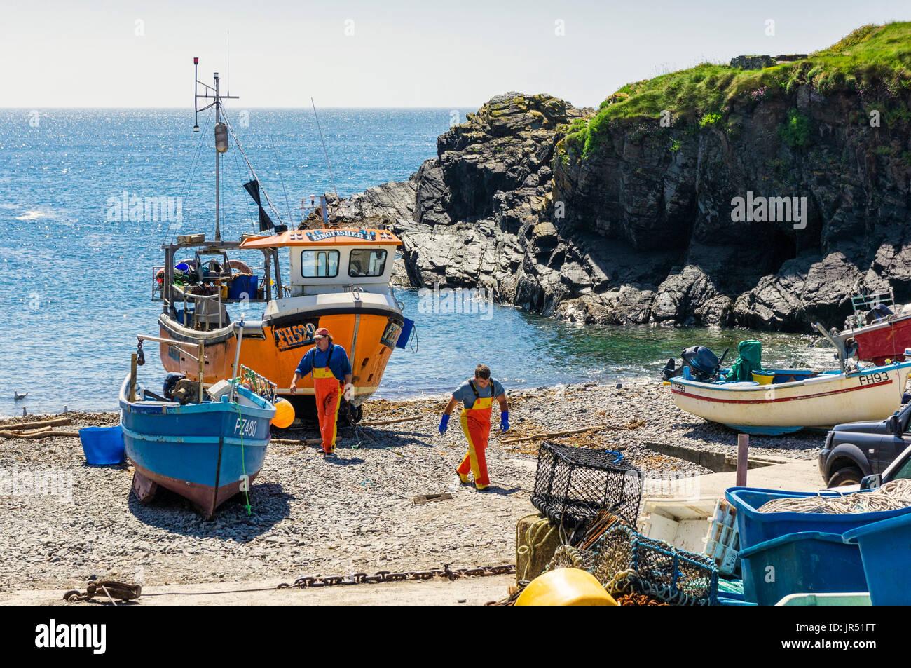 Fishing boat and fisherman at Cadgwith Cove, Lizard Peninsula, Cornwall, UK - Stock Image