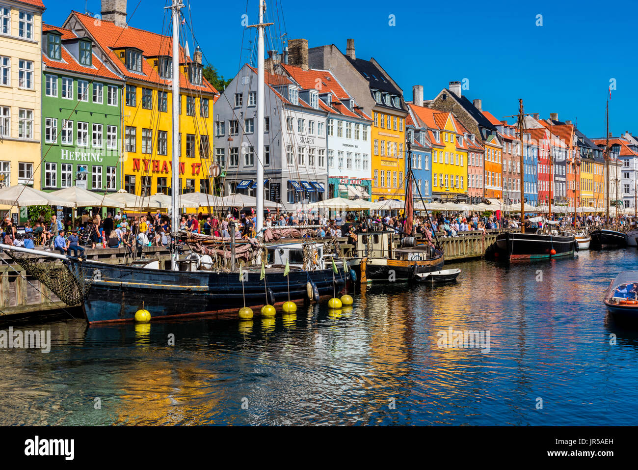 Nyhavn harbor and promenade in Copenhagen, Denmark. Nyhavn is the most famous landmark of Copenhagen. - Stock Image