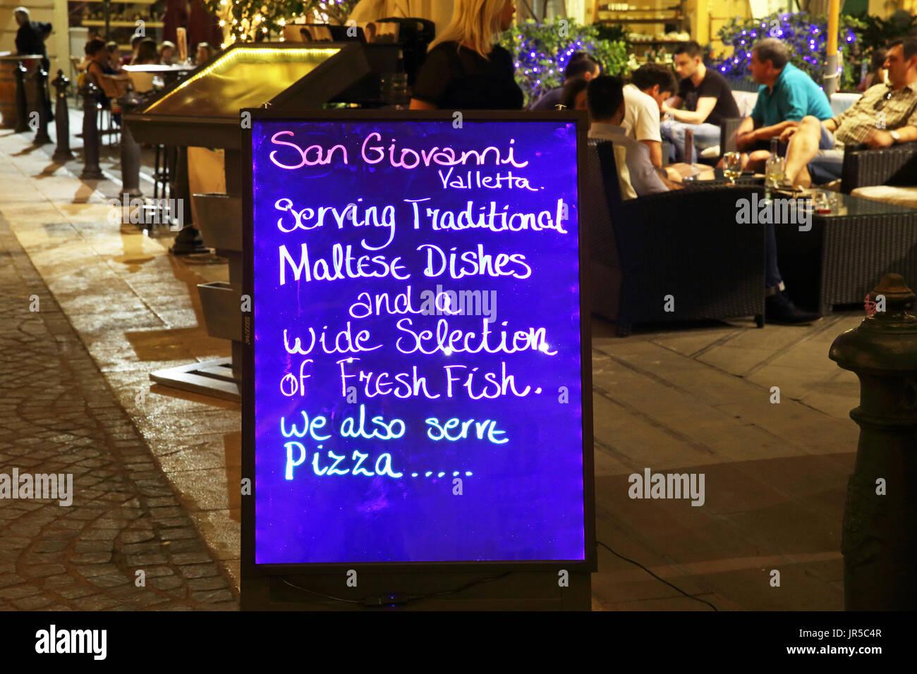 Restaurant menu on St John Square in the evening in Valletta, capital of Malta - Stock Image