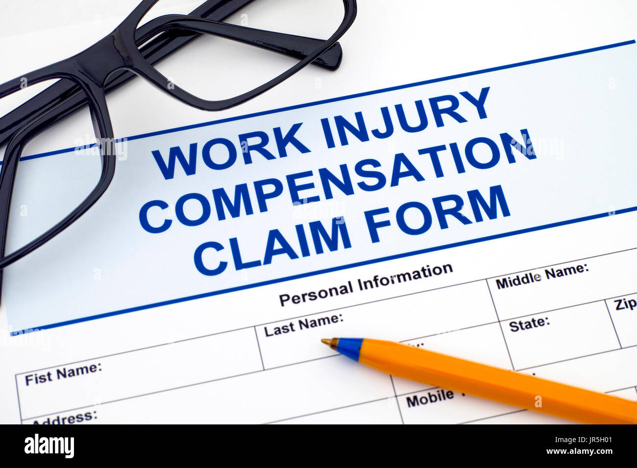 Work Injury Compensation Claim Form with ballpoint pen and glasses. - Stock Image