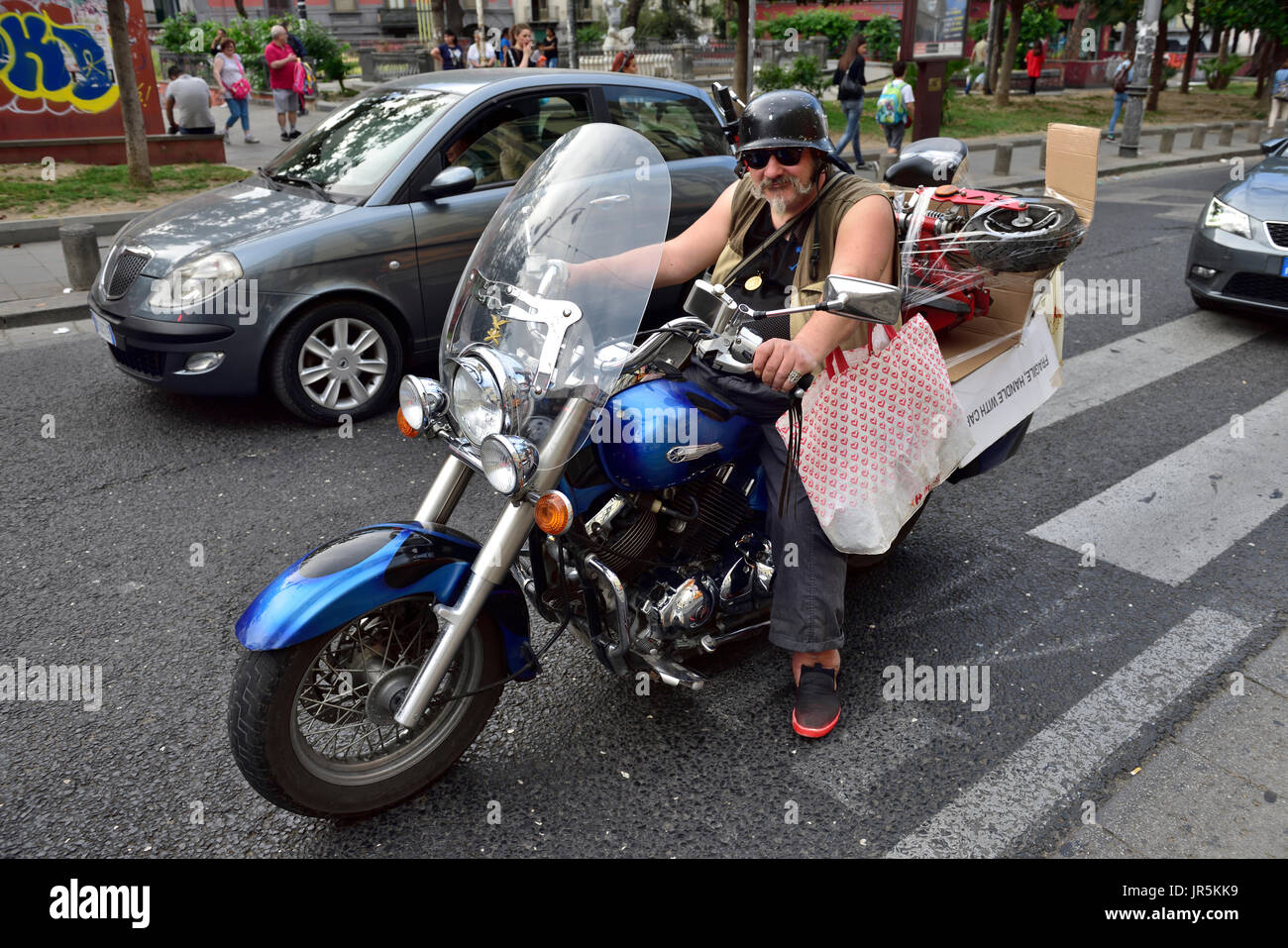 Man on motorcycle on Naples city street with large parcel - Stock Image