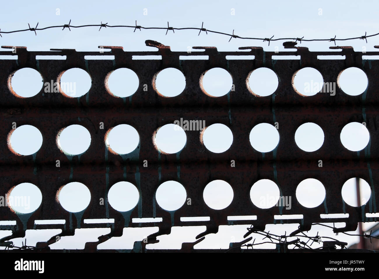 Barbed wire. Barbed wire on a fence of metal iron sheets with holes against blue sky to feel worrying - Stock Image