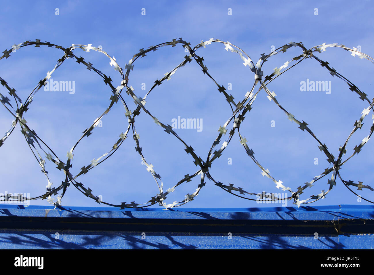 Barbed wire. Barbed wire on fence with blue sky to feel worrying - Stock Image