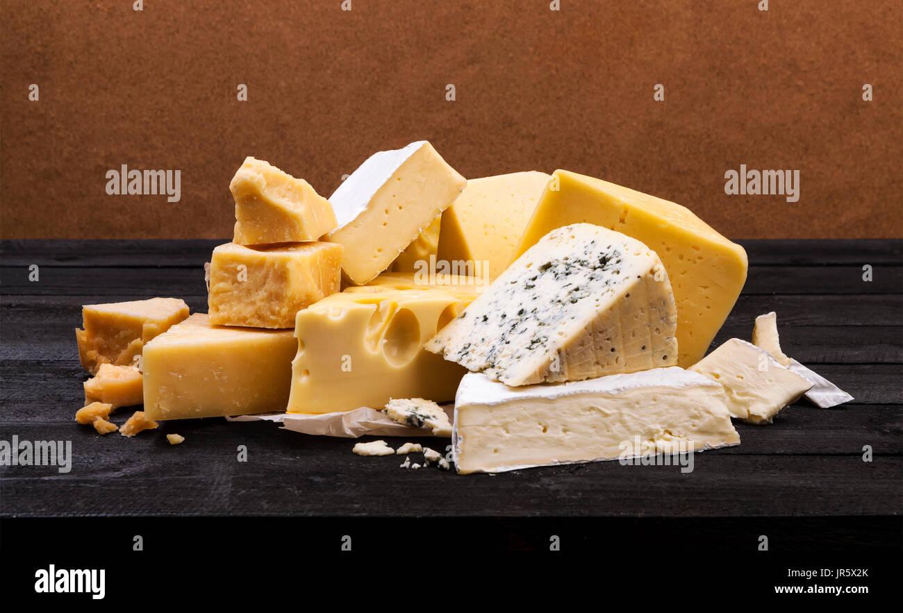 Various types of cheese on rustic wooden table - Stock Image