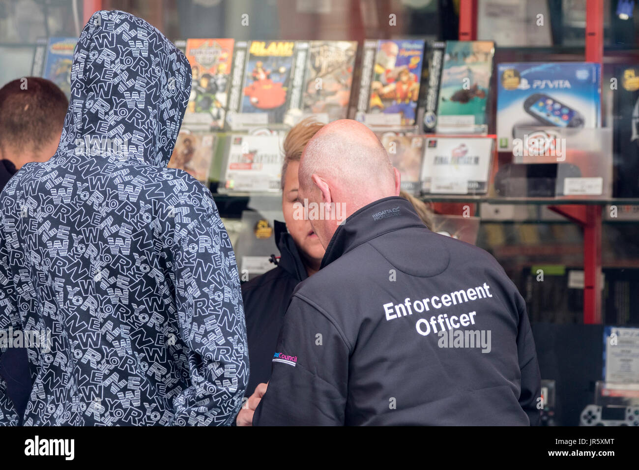 A civil enforcement officer issuing a fixed penalty notice for littering on the streets of Blackpool in Lancashire - Stock Image