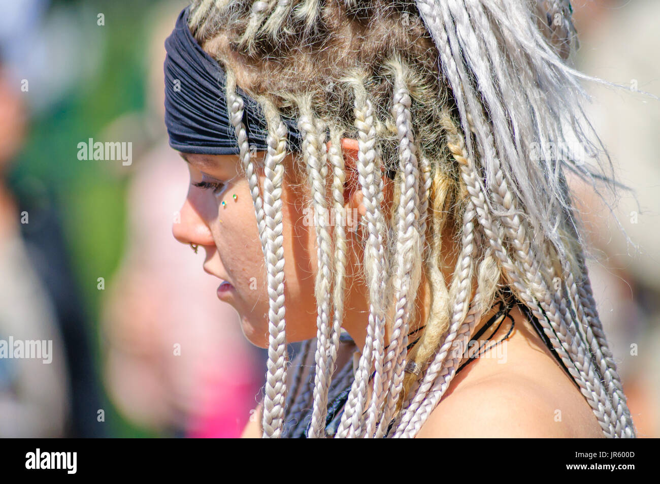 Female performer wearing a headband with braided dreadlock hairstyle and nose piercing in Edinburgh during the Carnival of The Jazz and Blues Festival - Stock Image