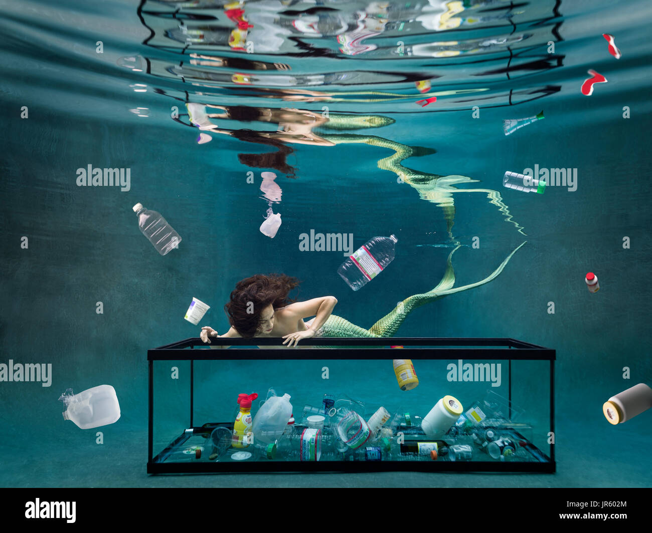Young mermaid looking at garbage floating in water - Stock Image
