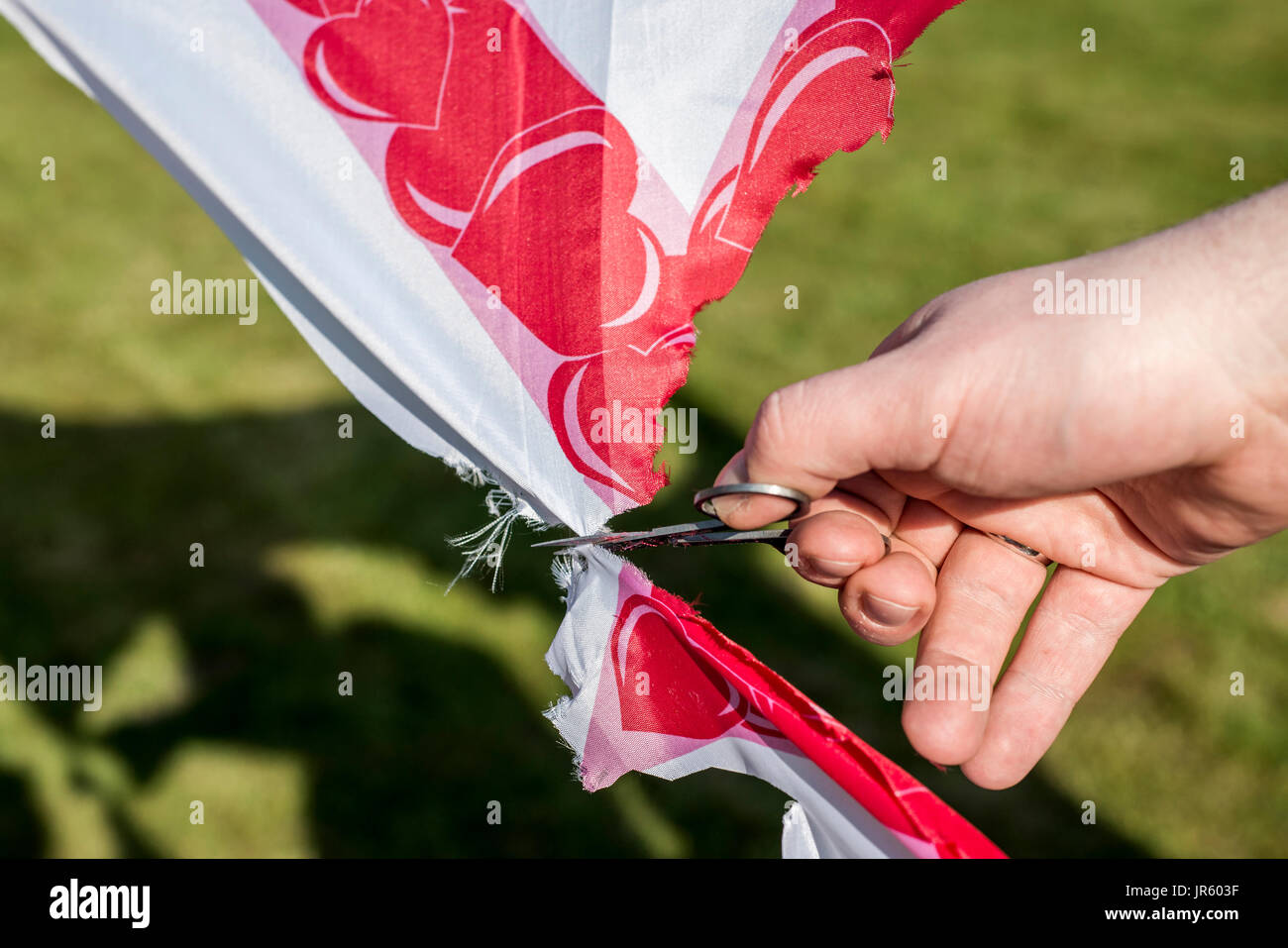 man cuts scissors finger hand on wedding tradition cutout heart detail closeup - Stock Image