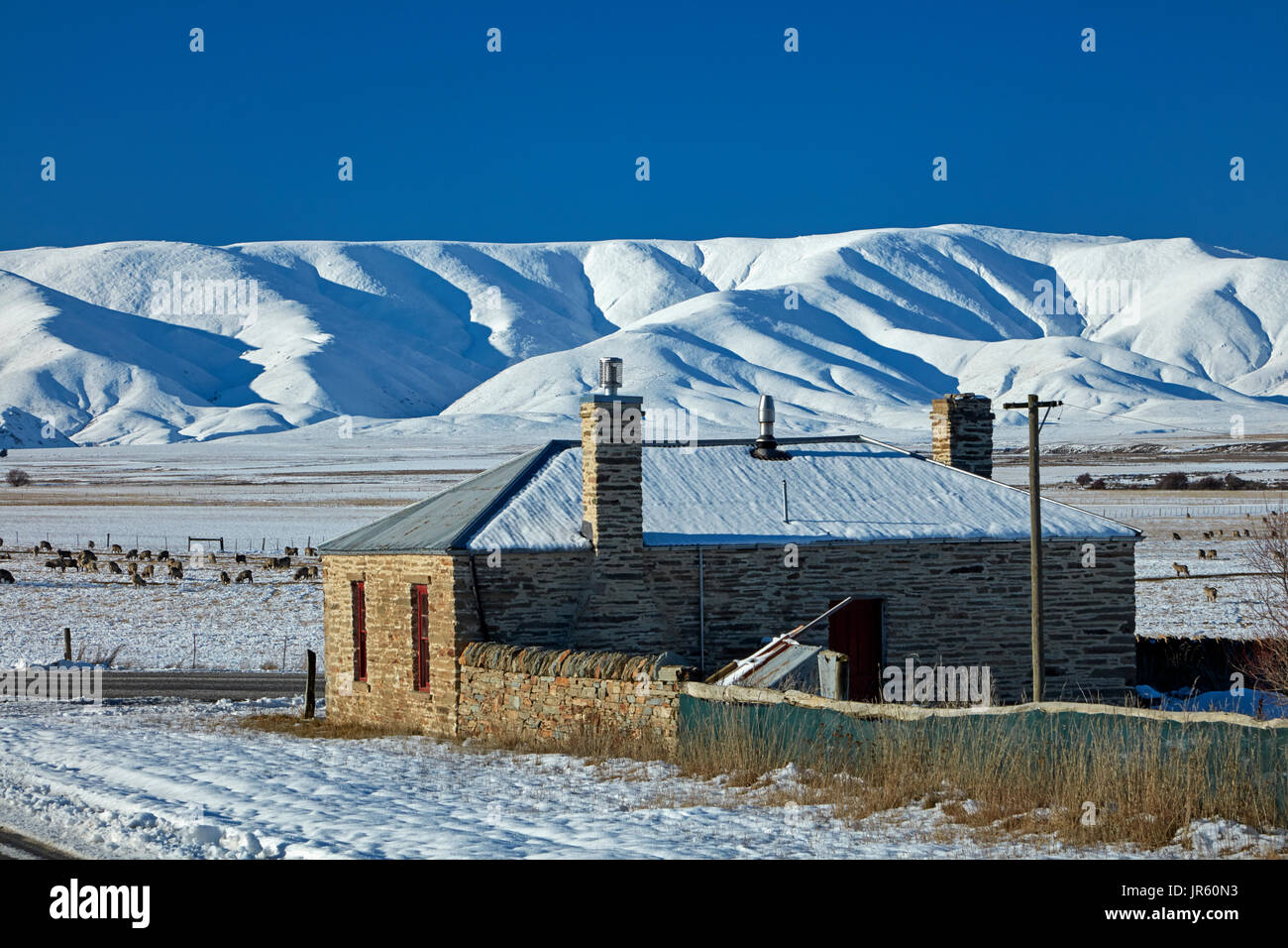 Historic stone cottage and Ida Range in winter, Hills Creek, Maniototo, Central Otago, South Island, New Zealand - Stock Image