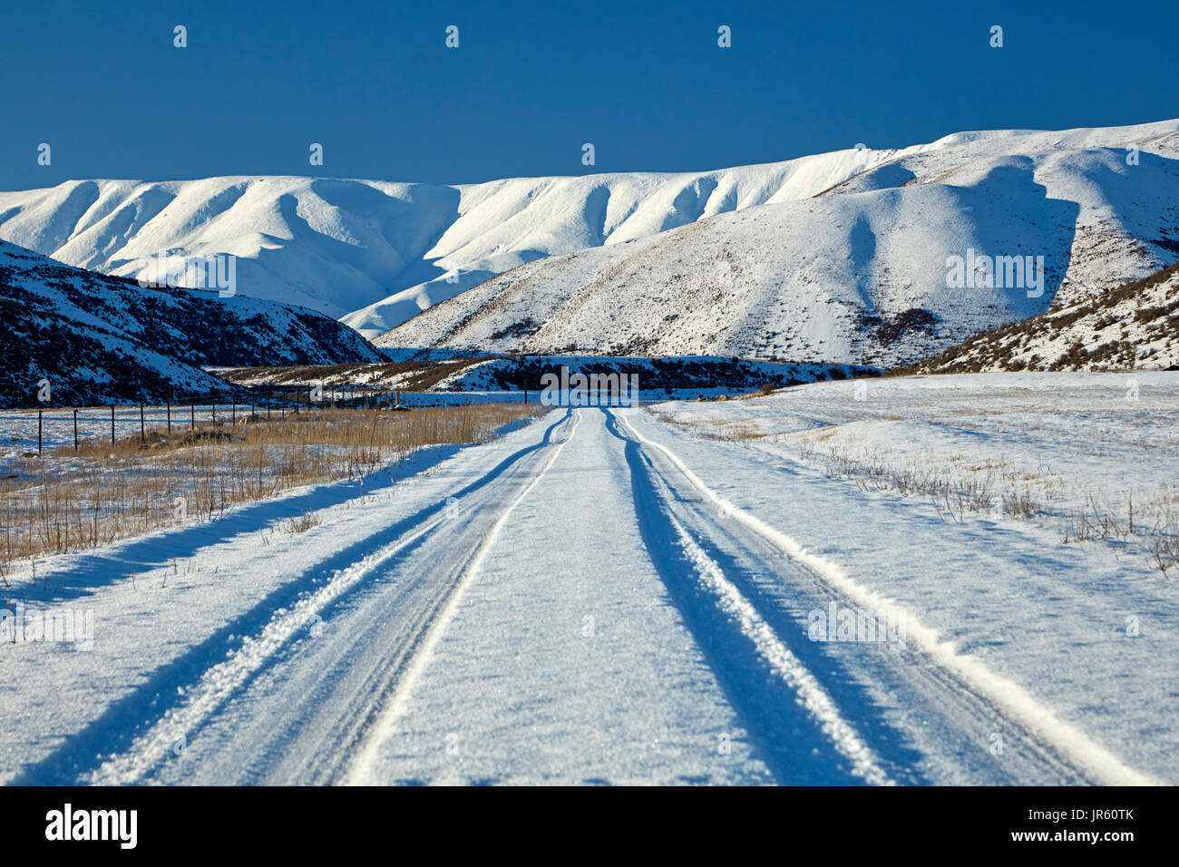 Hawkdun Range and snowy track to Falls Dam, Maniototo, Central Otago, South Island, New Zealand Stock Photo