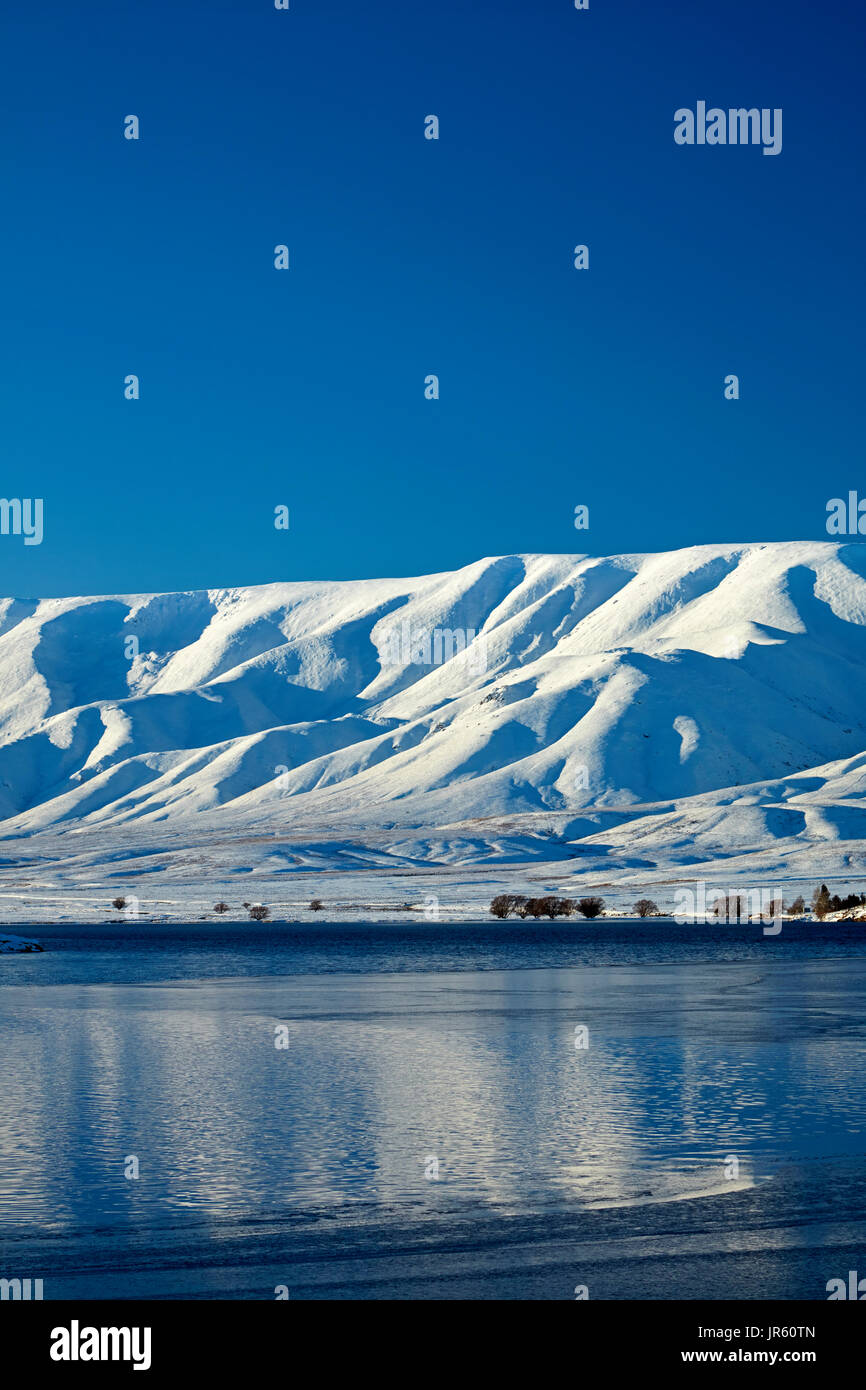 Falls Dam and Hawkdun Range in winter, Maniototo, Central Otago, South Island, New Zealand - Stock Image