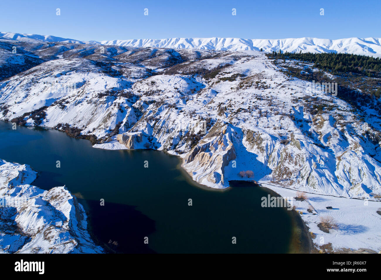 Snow around Blue Lake, St Bathans, and Hawkdun Range, Maniototo, Central Otago, South Island, New Zealand - drone aerial - Stock Image
