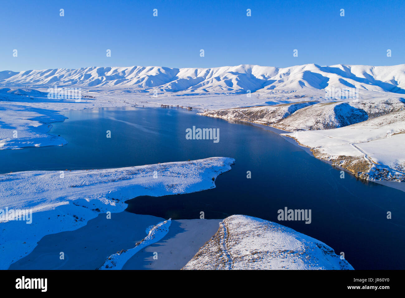 Ice at the edge of Falls Dam, and Hawkdun Range in winter, Maniototo, Central Otago, South Island, New Zealand - drone aerial - Stock Image