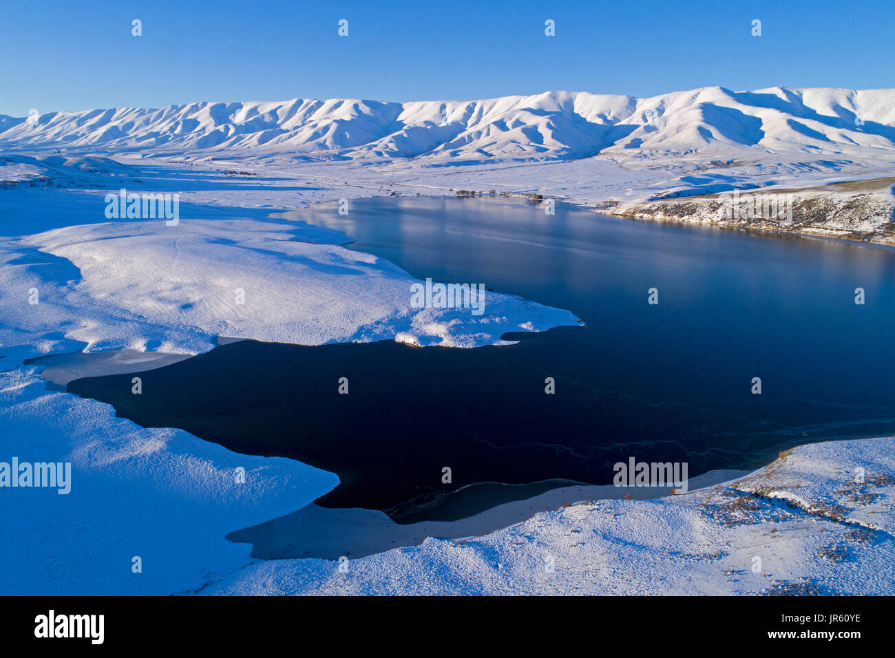 Falls Dam and Hawkdun Range in winter, Maniototo, Central Otago, South Island, New Zealand - drone aerial - Stock Image