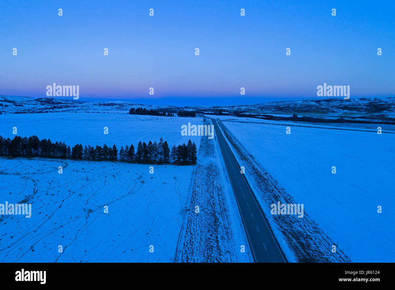 State Highway 85 in winter at sunset, near Oturehua, Maniototo, Central Otago, South Island, New Zealand - drone aerial - Stock Image
