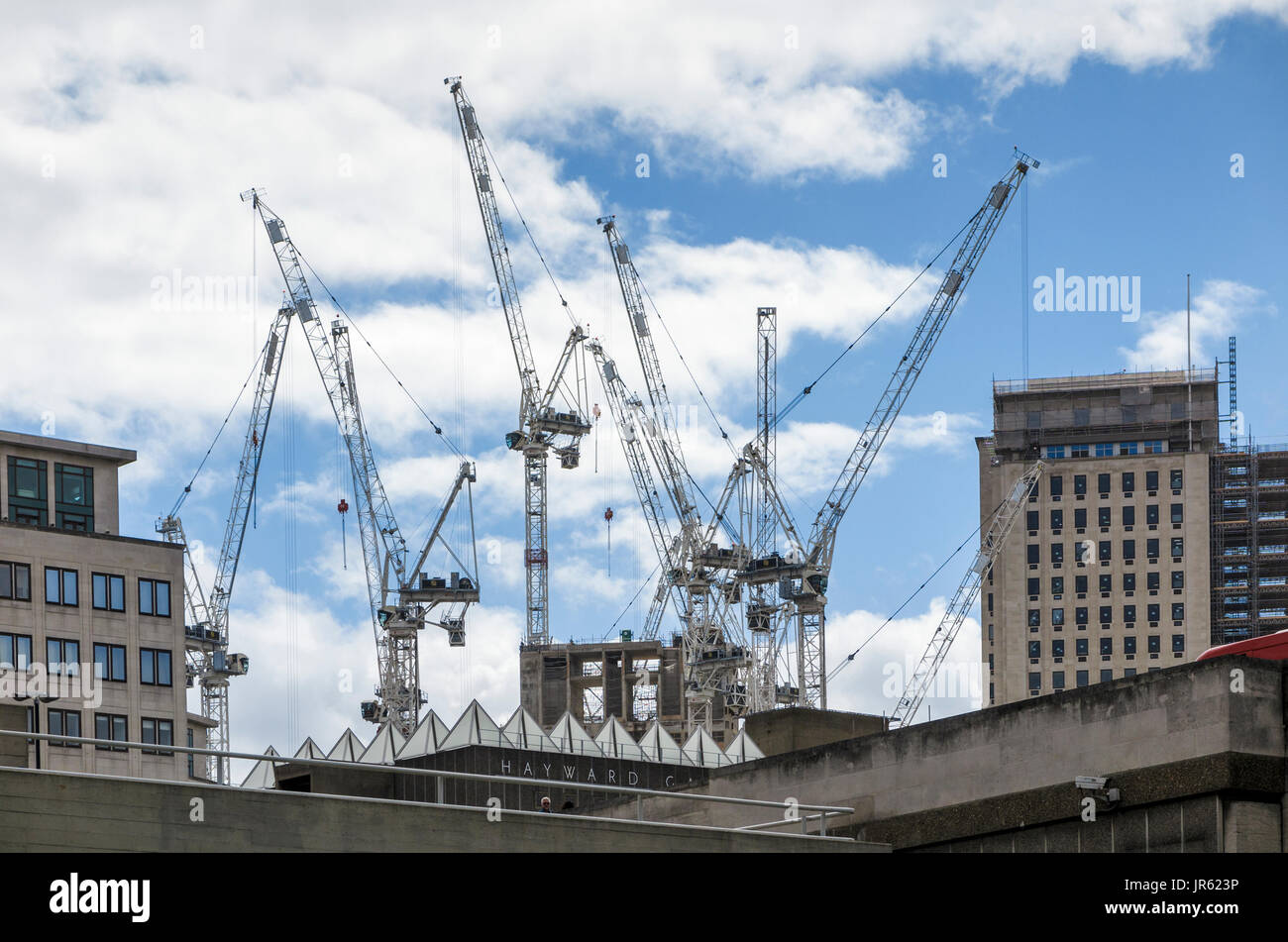 Tower cranes on the skyline at the partially built new Southbank Tower apartment block construction site, South Bank, Southwark, London SE1 - Stock Image