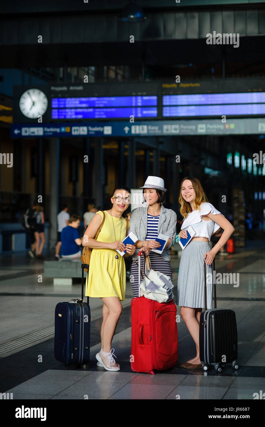 Three cute young women at the train station. They carry suitcases, passports and tickets. Girlfriends are happy at the beginning of an exciting journe - Stock Image