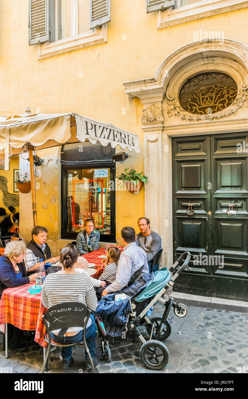 roman family having lunch at restaurannt pizzeria  alle muratte seated outdoors - Stock Image