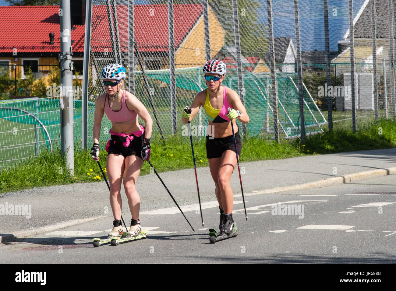Two women on Nordic roller skis rollerskiing on a road in summer. Typical Norwegian active lifestyle. Trondheim, Sør-Trøndelag, Norway, Scandinavia - Stock Image