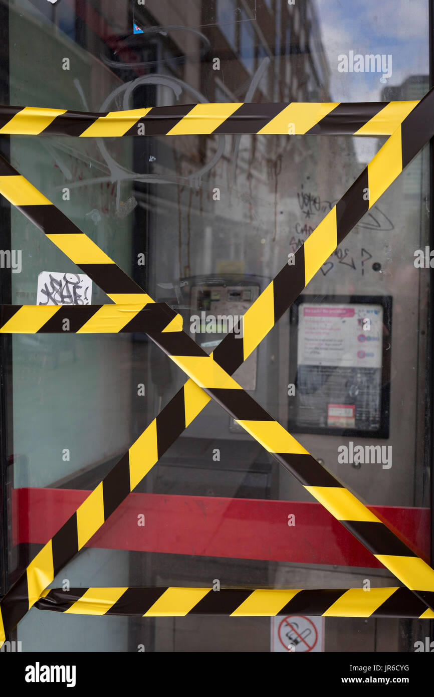 Hazard tape stretched across the glass of an old telephone kiosk on Tottenham Court Road, on 3rd August 2017, in London, England. - Stock Image