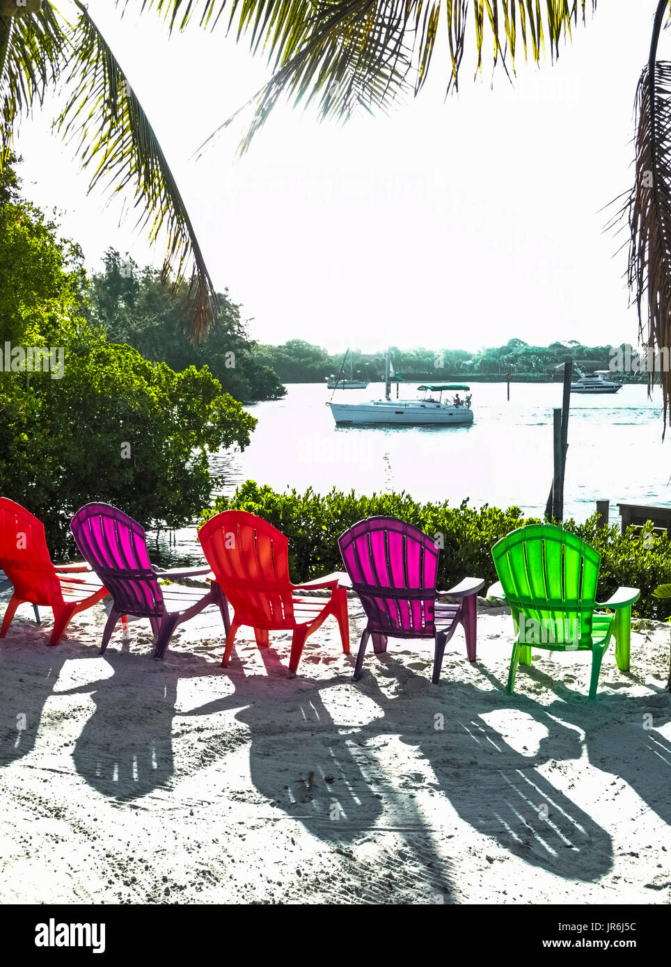 Colorful translucent plastic deck chairs invite relaxation and create shadows from the brilliant sunshine on a sandy waterfront along the Gulf Intracoastal Waterway in Sarasota County, Florida, USA. - Stock Image