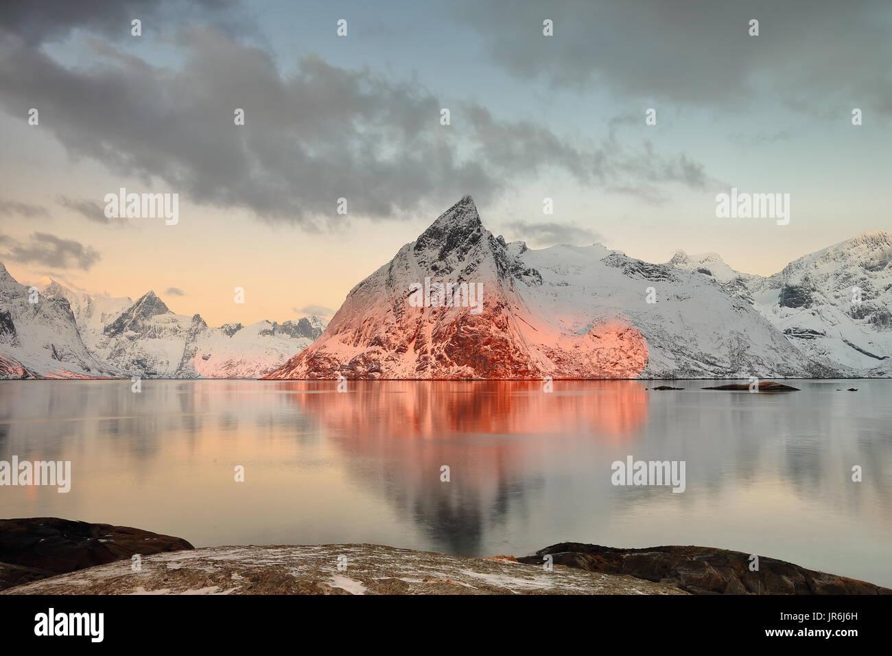 Reddish dawn-view to NW.from Toppoya island over Reinefjorden to Forsfjorden-Vorfjorden and Sauhagtindan-Klokkaattetinden-Brynliskartinden-Olstinden m - Stock Image