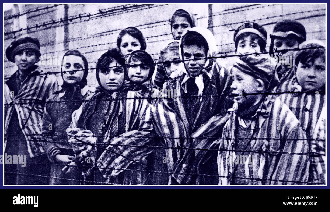 Child prisoners stare out from behind a barbed wire fence in notorious Nazi death-camp Auschwitz  Southern Poland. - Stock Image