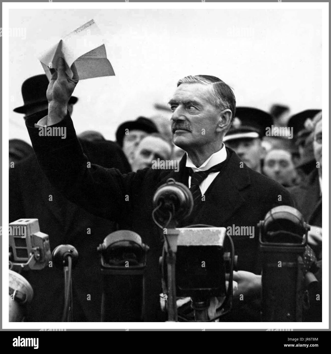 Neville Chamberlain holds 'the' piece of paper proudly aloft signed by both Hitler and himself on his return from Munich to Heston Aerodrome in 1938 with the quote; 'a desire never to go to war again...!' - Stock Image