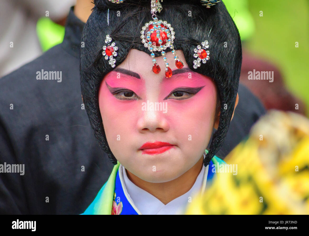 Young performer with painted face and jewelled headdress in Edinburgh during the Carnival of The Jazz and Blues Festival - Stock Image
