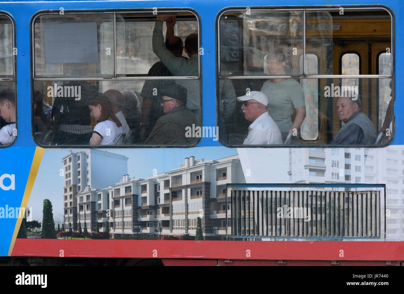 Passengers in a tram with advertisements on its side. Lviv, Ukraine - Stock Image
